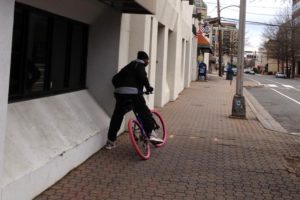 An alleged bike thief takes off on the victim's pink-tired bike (courtesy photo)
