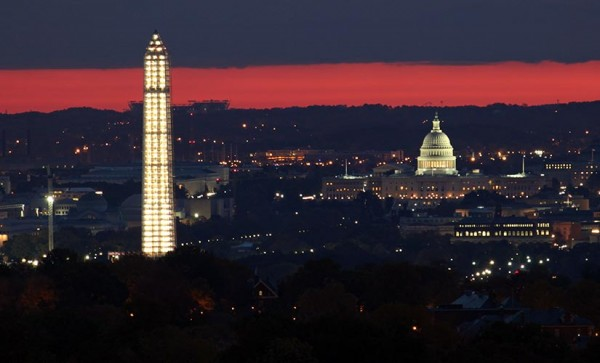 The Capitol and the Washington monument at sunrise, as seen from the top of a Ballston apartment building. FedEx Field and a Six Flags roller coaster are visible in the background. (Photo courtesy Andrew Clegg)