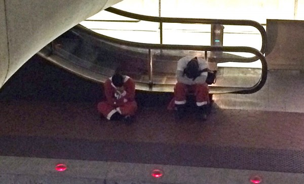 Tuckered out Santas at the Pentagon City Metro station