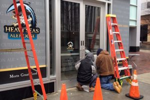 Workers affix signage to the door of the soon-to-open Heavy Seas Alehouse in Rosslyn