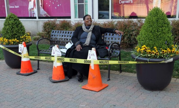 Unfazed by 'wet paint' signs, a woman sits on her favorite bench on Crystal Drive
