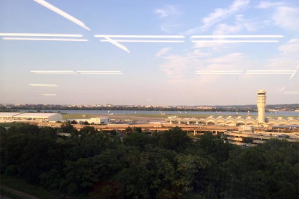 Fluorescent office lights can be seen as reflections in a window overlooking Reagan National Airport