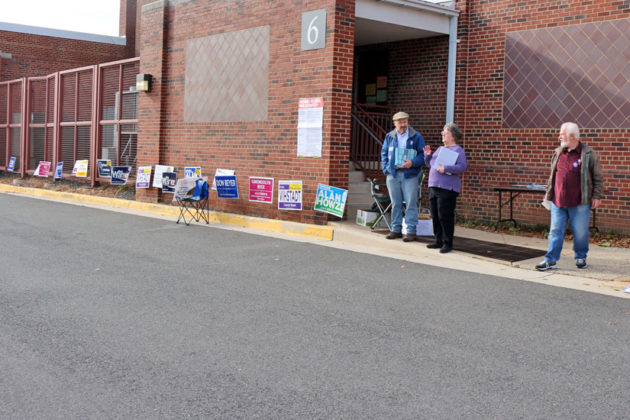 Campaign workers pass out sample ballots outside Arlington Traditional School