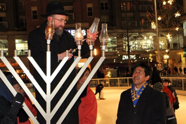 "Rabbi Mordechai Newman lights the menorah at ""Chanukah on Ice"" on Pentagon Row, as Walter Tejada watches"