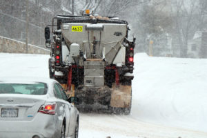 A salt truck drives on N. Park Drive with its plow up