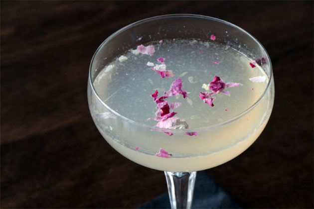 The Campos Rose, made of gin, St. Germain, lime juice and rose bitters, with rose petals on top