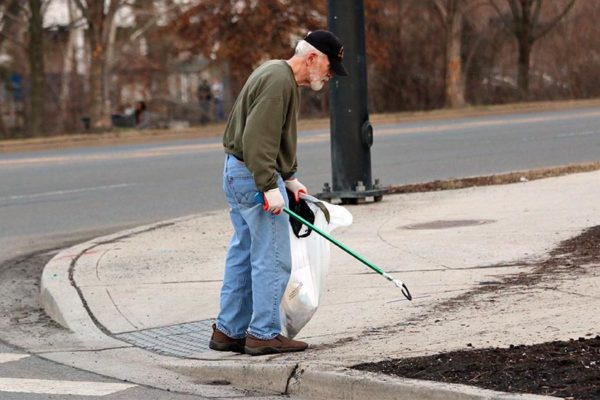 Man cleaning up trash on Four Mile Run Drive