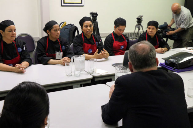 Sen. Tim Kaine hears about La Cocina VA from its trainees, in Spanish