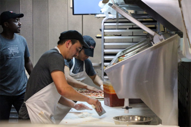 Cooks prepare the food at Wiseguy NY Pizza