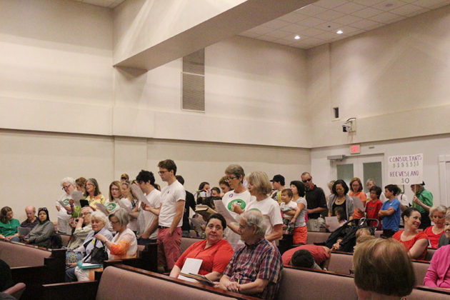 Protesters sing while County Board members get settled.