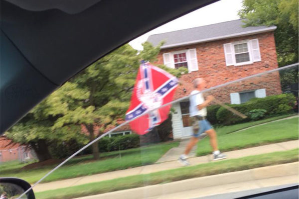 Man marching down Lee Highway with a Confederate flag (photo courtesy @WanyeVVest)