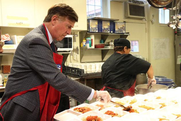 Rep. Don Beyer helps ladle food.