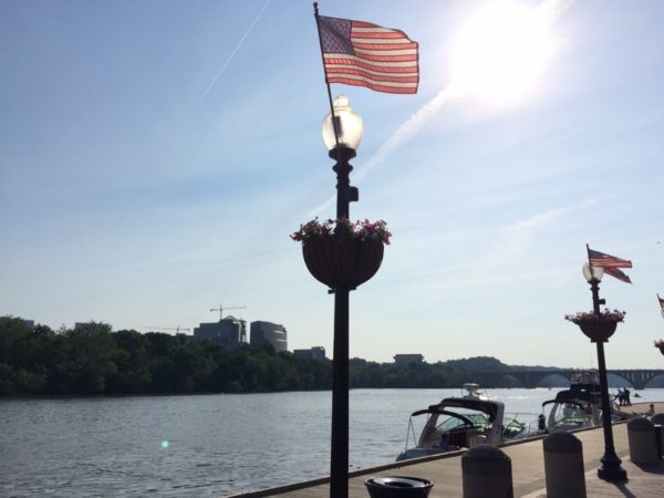 American flag at the Georgetown waterfront, with Rosslyn in the background