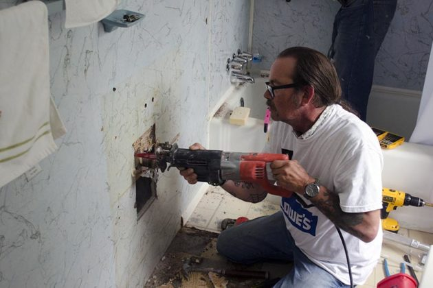 Volunteer from Rebuilding Together tries to find a leak during the home repair