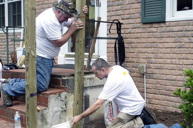 Volunteers from Rebuilding Together and Lowe's add a railing to the home during the home repair