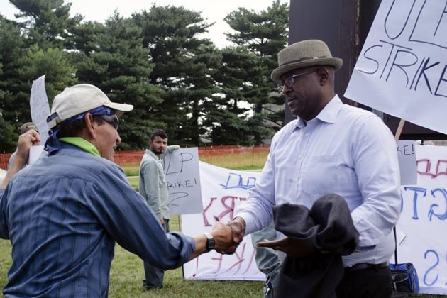 Christian Dorsey shakes hands with a worker at the Arlington Cemetery Groundkeepers Strike