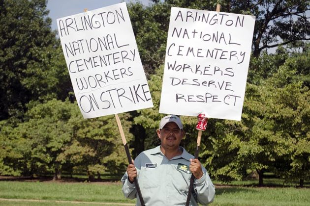 A worker holds up his signs at the Arlington National Cemetery Groundkeepers Strike