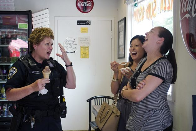 An ACPD officer jokes with locals inside Goody's during the Cones With a Cop event