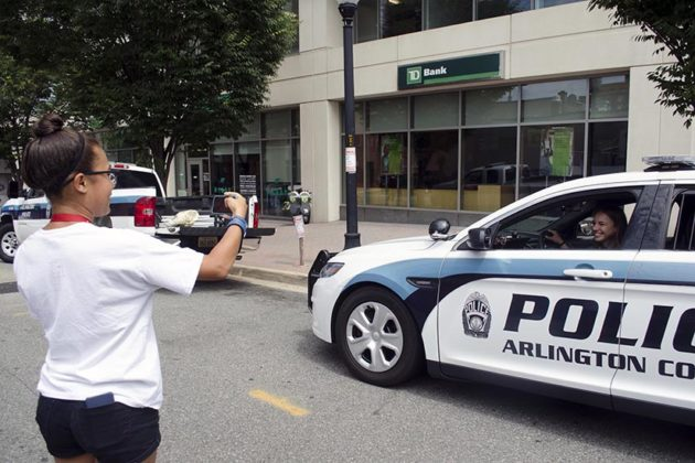 Two young women have a photo shoot in an ACPD car
