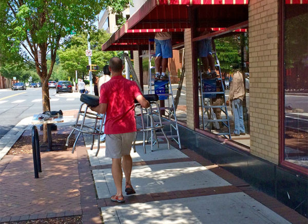 A man carries barstools away from Hard Times Cafe in Clarendon while workers remove the awnings