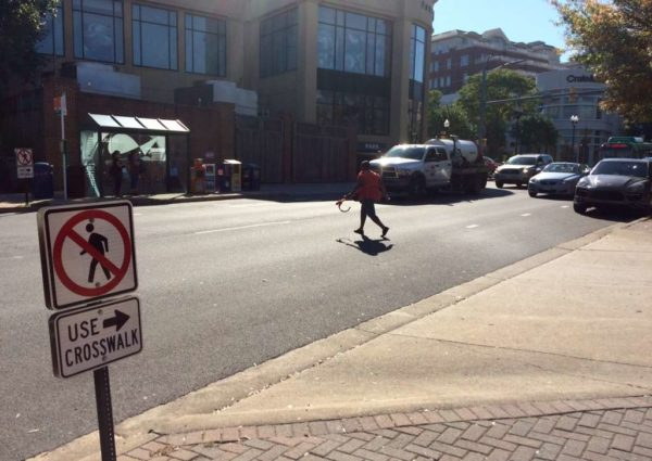 Pedestrian crossing the street in Clarendon in front of traffic