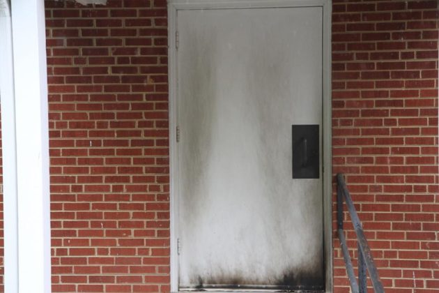 Burned door at Kingdom Hall of Jehovah's Witnesses church