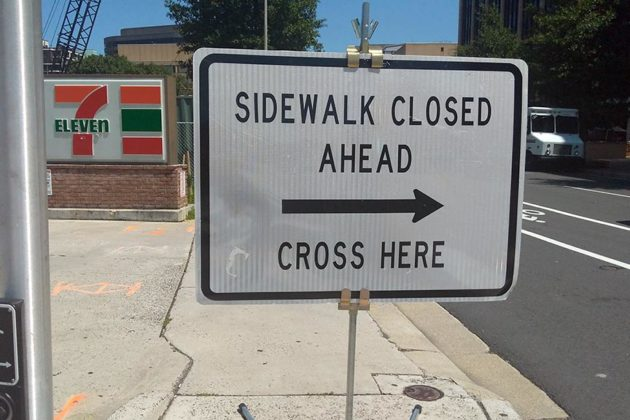 Pedestrians are directed to cross onto the opposite side of Wilson Blvd
