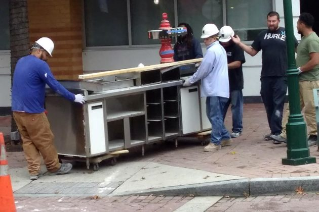 Workers hauling equipment at the future Big Buns location in Shirlington