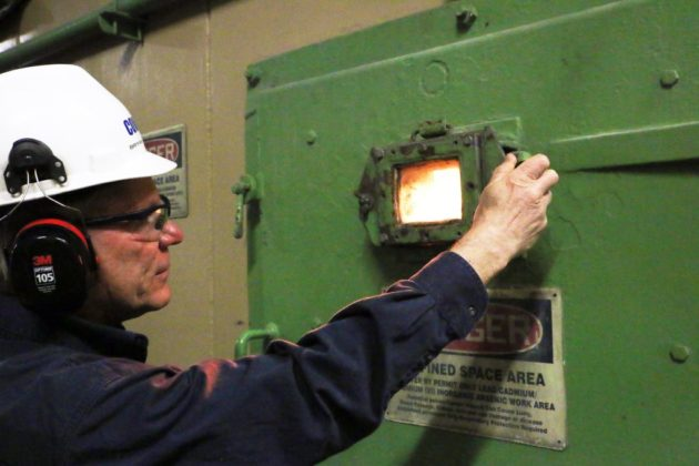 Facility Manager Bryan Donnelly inspects the combustion chamber