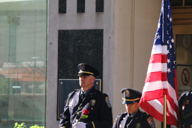 An Arlington County police officer offers a rose for a fallen officer.