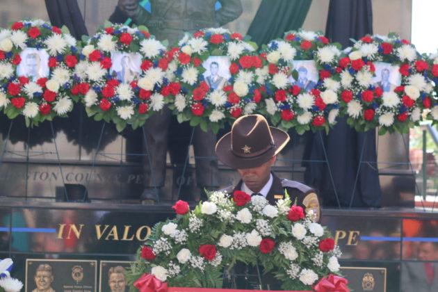 An Arlington County sheriff's deputy presents a wreath.