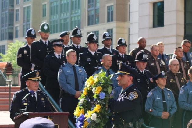 An Arlington County police officer presents a wreath.